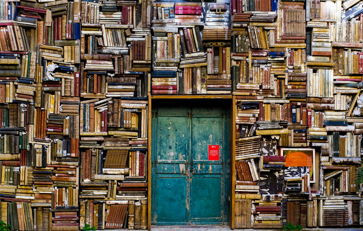 Green double doors in a large wall of books.